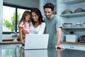 Smiling parents using laptop with daughter Royalty Free Stock Photo