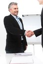 Smiling people shaking hands in office. Royalty Free Stock Photo