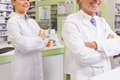 Smiling pharmacist and his trainee with arms crossed in the pharmacy Stock Images