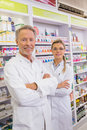 Smiling pharmacist and his trainee with arms crossed in the pharmacy Stock Photos