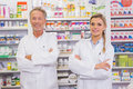 Smiling pharmacist and his trainee with arms crossed in the pharmacy Stock Image