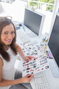 Smiling photo editor at work holding contact sheet sitting desk Royalty Free Stock Photography