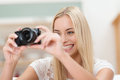 Smiling photographer taking a photograph beautiful young female with digital camera indoors Royalty Free Stock Images