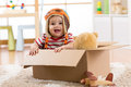 Smiling pilot aviator baby boy with teddy bear toy plays in cardboard box Royalty Free Stock Photo