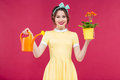 Smiling pinup girl holding flowers in pot and watering can Royalty Free Stock Photo