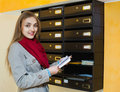 Smiling positive girl in outwear receiving correspondence at hall entrance Stock Image