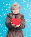 Smiling pre teen girl in winter clothes with red heart snow falls Stock Image