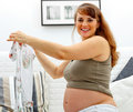 Smiling pregnant female with baby clothes in hands Stock Photo