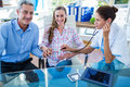 Smiling pregnant woman and her husband with doctor women in clinic Stock Photography