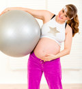 Smiling pregnant woman holding fitness ball Stock Photo