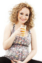 Smiling pregnant woman holding glass of juice in h Royalty Free Stock Photo