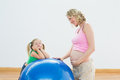 Smiling pregnant woman with young daughter women in a fitness studio Royalty Free Stock Photos