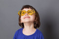 Smiling preschool child wearing yellow heart-shape glasses Royalty Free Stock Photo