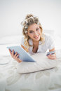 Smiling pretty blonde wearing hair curlers shopping online lying on cosy bed Royalty Free Stock Image