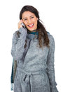 Smiling pretty brunette wearing winter clothes on the phone white background Stock Images