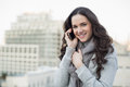 Smiling pretty brunette in winter clothes having phone call outside on a cloudy day Stock Photography