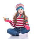 Smiling pretty little girl wearing coloful knitted scarf, hat and gloves, holding christmas gift isolated on white background. Royalty Free Stock Photo