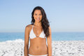Smiling pretty long haired woman in white bikini posing on the beach Stock Image
