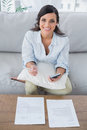 Smiling pretty woman doing her accounts in living room Stock Images