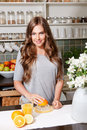 Smiling pretty woman making orange juice Royalty Free Stock Photo