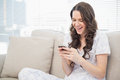Smiling pretty woman in pyjamas reading a text on her smartphone while sitting cosy sofa Royalty Free Stock Images
