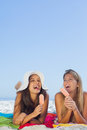 Smiling pretty women lying on their towel eating ice cream having holidays together Stock Photos