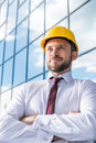 Smiling professional architect in hard hat against building Royalty Free Stock Photo
