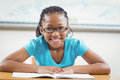Smiling pupil reading book in a classroom portrait of school Stock Photos
