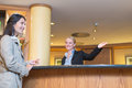 Smiling receptionist helping a hotel guest low angle view of beautiful friendly behind the service desk in lobby an attractive Stock Image