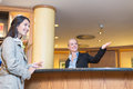 Smiling receptionist helping a hotel guest low angle view of beautiful friendly behind the service desk in lobby an attractive Stock Photography