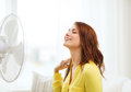 Smiling redhead teenage girl with big fan at home summer weather and equipemt concept Stock Photo