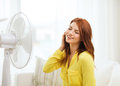 Smiling redhead teenage girl with big fan at home summer weather and equipemt concept Royalty Free Stock Photo