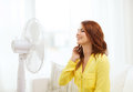 Smiling redhead teenage girl with big fan at home summer weather and equipemt concept Royalty Free Stock Image
