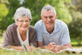 Smiling relaxed senior couple lying in park Royalty Free Stock Photography