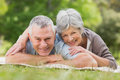 Smiling relaxed senior couple lying in park Stock Image
