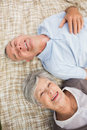 Smiling relaxed senior couple lying in park high angle view of a the Stock Photos