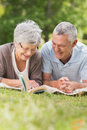 Smiling relaxed senior couple lying in park portrait of a the Royalty Free Stock Image