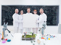 Smiling researchers in lab close up of five scientists a chemistry holding hands an empty banner and confident looking the camera Royalty Free Stock Image