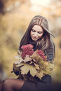 Smiling romantic girl with bouquet in autumn park the Stock Images