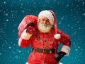 Smiling Santa Claus carrying big bag full of gifts to children on blue background. Royalty Free Stock Photo