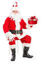 Smiling santa claus on a chair holding a present isolated white background Royalty Free Stock Images