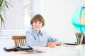 Smiling school boy doing his homework sitting at a white desk Stock Images
