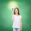 Smiling school girl pointing finger to light bulb education energy saving advertising and people concept little in white blank t Royalty Free Stock Image