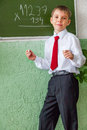 Smiling schoolboy at blackboard with chalk Royalty Free Stock Photography