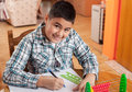 Smiling schoolboy writing homework selective focus on face Stock Photography