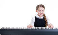 Smiling schoolgirl plays on the electric piano. Royalty Free Stock Photo