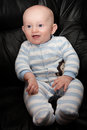 Smiling seated baby chubby boy with blue eyes and surprised expression on his face sitting up Royalty Free Stock Image