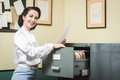Smiling secretary searching files in the filing cabinet vintage drawers Royalty Free Stock Image