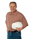 Smiling senior architect holding white safety hat Royalty Free Stock Photo