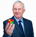 Smiling senior business man holding a  cube Stock Photos